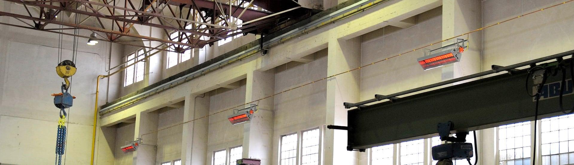 Mehrere Hellstrahler der Firma Schwank an der Wand einer Produktionshalle.