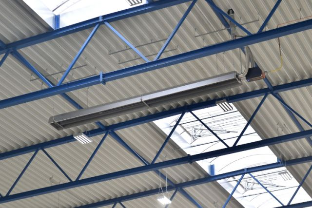 Dunkelstrahler deltaSchwank an Hallendach mit blauen Stahlträgern.