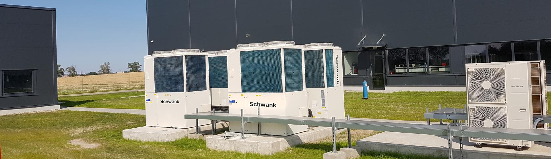 Vier Gaswärmepumpen von Schwank vor einer Halle.