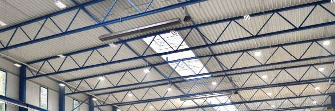 Zwei Dunkelstrahler von Schwank unter dem Dach einer Industriehalle als Hallenheizung.